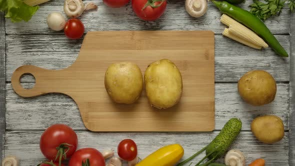 Thumbnail for Two Fruits of Potatoes Lie on a Cutting Board. Men's Hands Taking Potato Simultaniosly