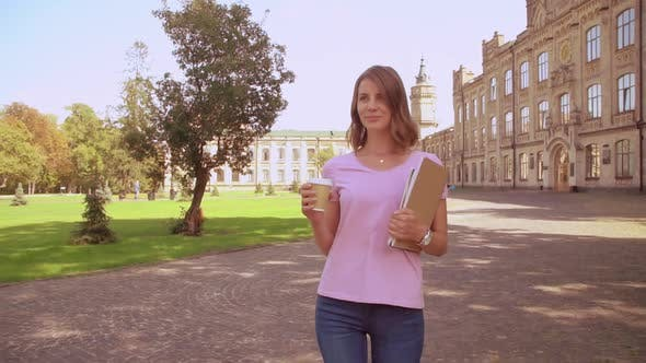 Thumbnail for Woman with Notebooks Drinking Tea Walks in Campus Area