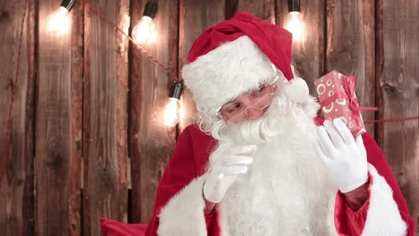 Cover Image for Santa Claus Shaking a Small Gift Tryring To Guess What's Inside