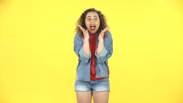 Thumbnail for Very Surprised Girl with Shocked Wow Face Expression on Yellow Background at Studio