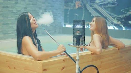 Beautiful and Sexy Girls Smoke Hookah in the Pool