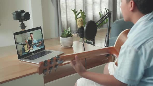 Boy Playing Guitar And Sing A Song While Streaming On Computer Laptop