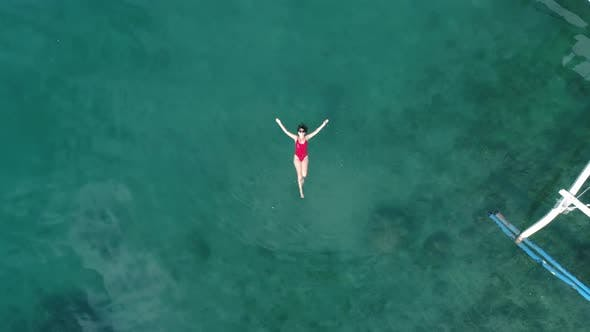 Thumbnail for Top View of Young Pretty Sexy Girl in Red Swimsuit Floating on Water Surface in Crystal Clear