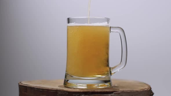 Slow Motion Shot of Light Beer Is Poured Into a Beer Glass with a Handle, a Lot of Bubbles and Foam