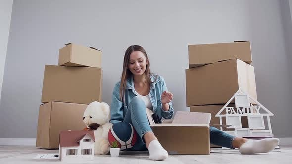 Thumbnail for Girl Having Fun Alone while Unpacking Box After Relocation in Her New Bought Flat