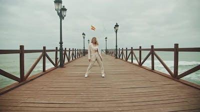 Young Woman Dancing Along Pier At Seaside