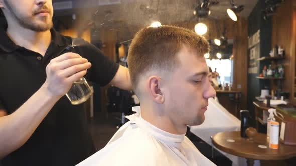 Young Hairstylist Spraying Water on Male Hair From Sprayer After Cutting in Barbershop. Hairdresser
