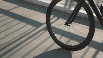Silhouette of bike wheel in sunset light. Girl is pedaling bike, close up of bike gear.