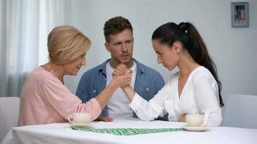 Helpless Man Looking at Mother and Wife Arm Wrestling Competition, Battle
