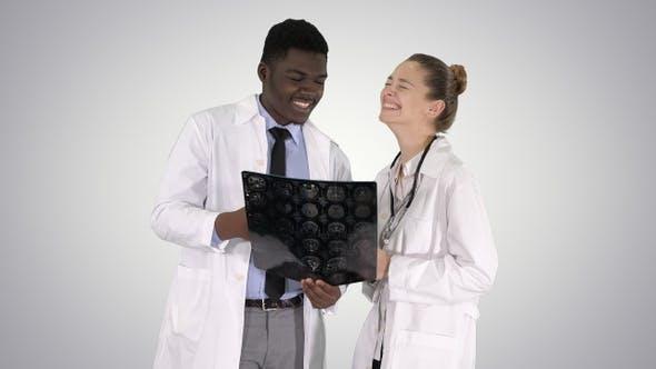 Thumbnail for Lachende Ärzte studieren Röntgenaufnahme auf Gradientenhintergrund.