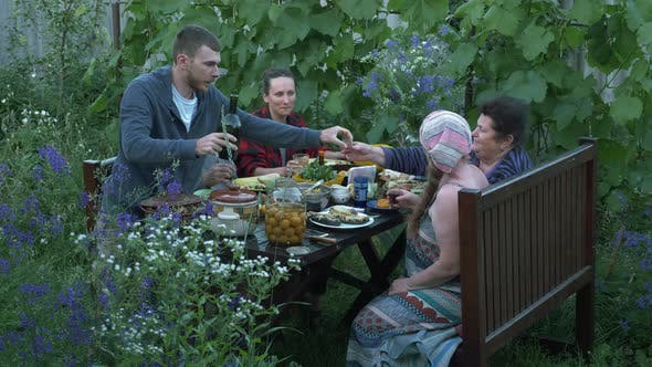 Thumbnail for Big family picnic party outdoor. Happy relatives at dining table on courtyard at summer