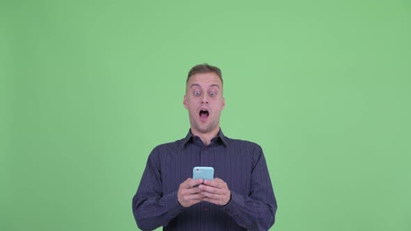 Thumbnail for Face of Happy Handsome Businessman Using Phone and Looking Surprised