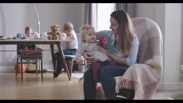 Thumbnail for Happy Young Caucasian Mutter sitzt auf Schaukelstuhl mit Ihr Baby Tochter während zwei weitere Kinder