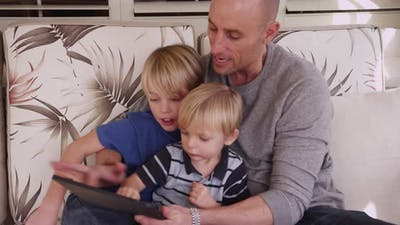 Two young brothers reading an ebook with their father