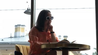 Young Woman Reading Book in Cafe Next to Window