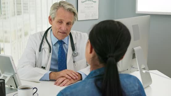 Thumbnail for Senior doctor in his office talking to new patient about health care options
