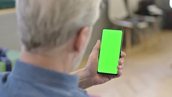 Old Man Using Green Mock-up Screen Smartphone