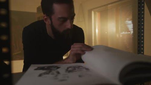 Artist Analyzing a Sketch in A Sketchbook