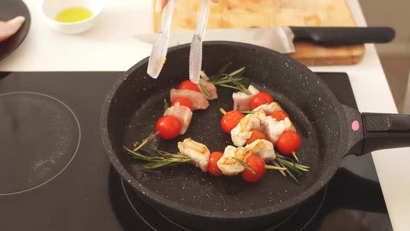 Thumbnail for Close Up of Chicken Kebabs Served with Tomato Cherry and Rosemary on Frying Pan