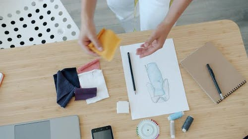 Closeup of Woman Clothes Designer Choosing Fabric for New Garment Looking at Sketch Picture