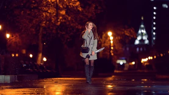 Jolie fille marche le long de l'allée avec un parapluie