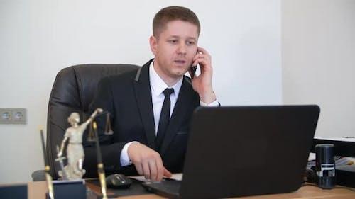 Erfolgreicher Anwalt nimmt einen Anruf in seinem Büro. Sprechen Sie Telefon mit dem Kunden und versuchen zu erklären