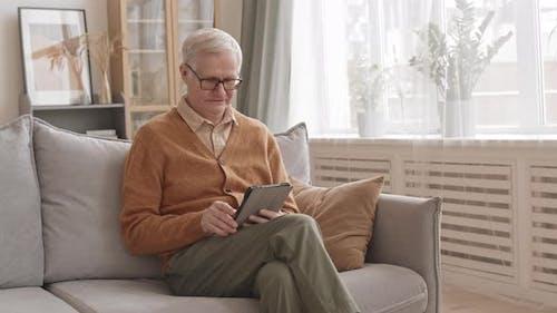 Älterer Mann mit digitalem Tablet zu Hause