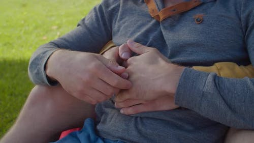 Close-up of Gay Couple Caressing Hands Outdoors