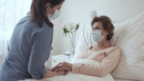 Home Caregiver With Face Mask Holding Hands of Female Senior Patient Lying in Bed at Nursing Home