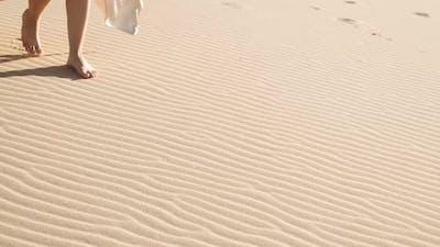 Woman Walking Barefoot Over Rippled Sandy Beach