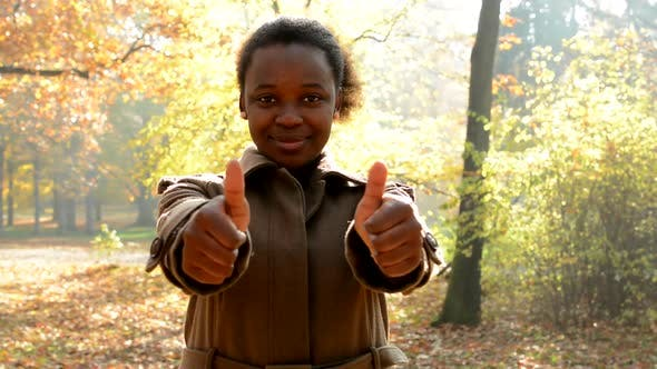 Thumbnail for Young Beautiful Happy African Girl Stare Into Camera, Shows Two the Thumbs-up and Stands in Woods