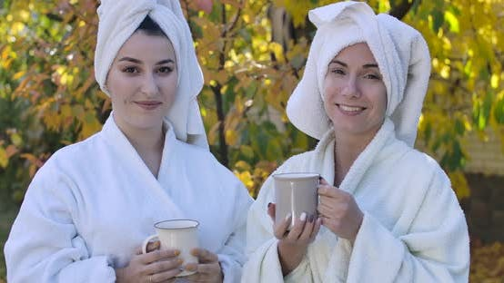 Thumbnail for Two Young Cute Caucasian Women in Bathrobes and Hair Towels Standing Outdoors, Looking at Camera