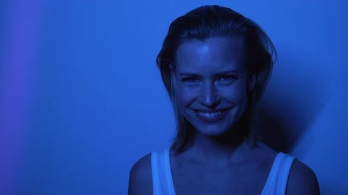 Beautiful Model in Front of Wall Laughing While Inside Dark Room
