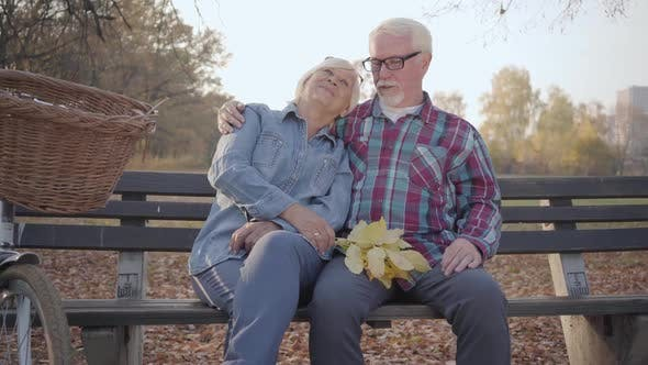 Thumbnail for Portrait of a Happy Caucasian Retired Couple Sitting on the Bench in Sunlight and Talking