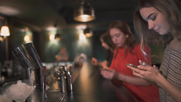 Thumbnail for Three Busy Young Girls Sit By the Bar Waiting for Cocktails and Typing Messages in Their Smatphones