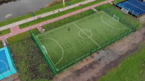 People playing football on green artificial soccer field outdoors. Boys play soccer outside