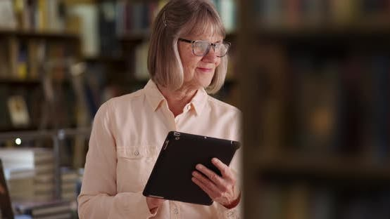 Charming senior woman using handheld tablet device in library setting