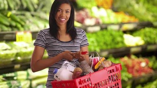 Cheerful female at supermarket holding basket, smiling at camera