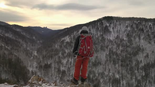 Thumbnail for A Lone Young Male Hiker Stands on Top of a Mountain at Sunset.