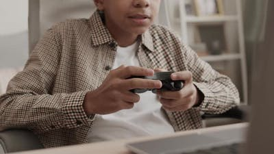 Boy Playing Game with Console Controller