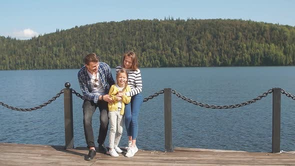 Thumbnail for Portrait of Happy Family: Mother, Father and Child Outdoors. Beautiful Sporty Family Spends the Fall