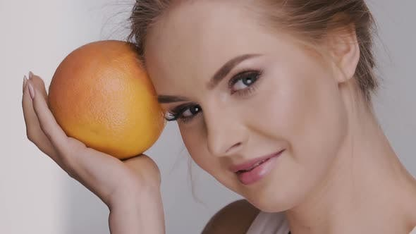 Thumbnail for Fresh Female Face with Juicy Orange Laughing and Looking To the Camera