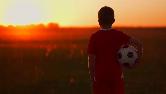 Thumbnail for Boy with a Ball in a Field at Sunset, Boy Dreams of Becoming a Soccer Player, Boy Goes To the Field