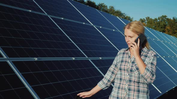 Thumbnail for Woman with Smartphone Goes Aquarius Solar Panels at Home Solar Power Plant
