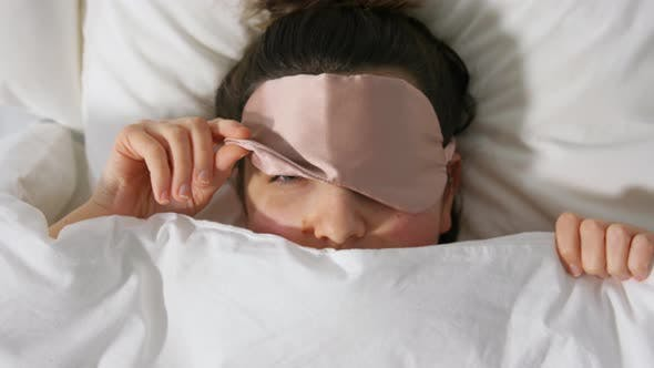 Thumbnail for Woman with Eye Sleeping Mask in Bed Under Blanket