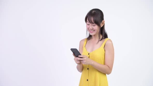 Thumbnail for Happy Beautiful Asian Woman Smiling While Using Phone