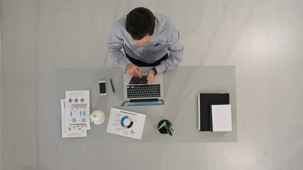 Thumbnail for Top View of Businessman Using a Digital Touch Screen Tablet and Working at Office Desk