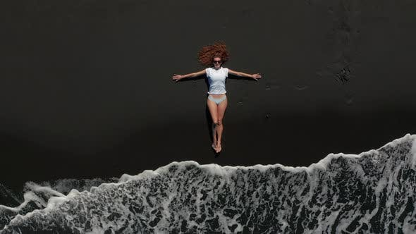 Thumbnail for Aerial View. Beautiful Woman Lay Down and Rest on the Black Beach in Tenerife While a Long Oceanic