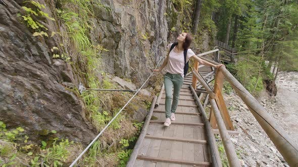 Thumbnail for Woman with a Backpack Walking on a Wooden Bridge in a Mountain Forest