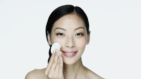 Thumbnail for Young woman cleansing her face with cotton pad